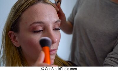 make-up artist applies powder and makes the correction of the face shape to the girl