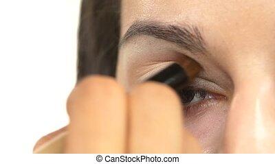 Make-up artist applying a light brown shadows, close up -...