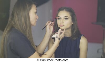 Make up artist applying a toning cream to a model s face in a studio