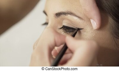 Make up artist applying black eyeliner to a fair hair girl s eye