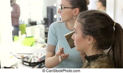 Make-up artist applying cosmetics to model