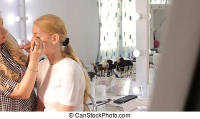 Make-up artist applying cosmetics to model.