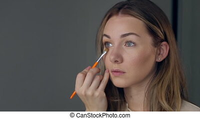 Make-up artist applying eye shadow with brush, close up.