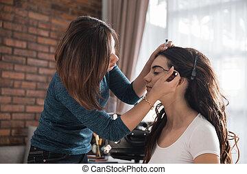 make up artist applying eyebrow shaping to caucasian beautiful model