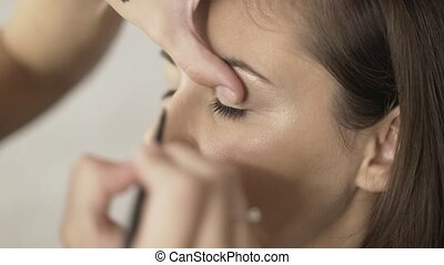 Make up artist applying eyeliner to a fair hair girl s eye