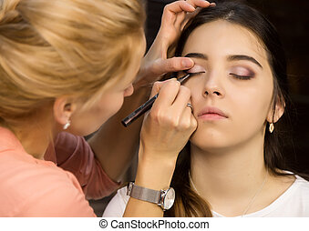 Make-up artist applying liquid eyeliner with brush to beautiful woman face. Make up in process