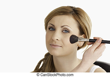 Make-up artist applying make up to an attractive blond-haired woman in a studio