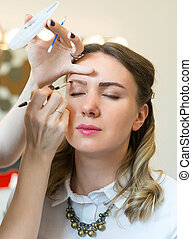 Make-up artist applying makeup on model's face.