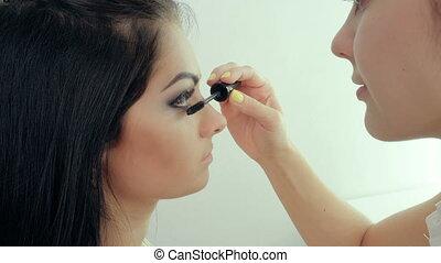 Make-up artist applying makeup to model's eye. Close up...