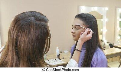 Make-up artist applying powder with a brush on model's cheeks