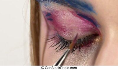 Make-up artist applying purple color eyeshadow on close  model's eye, exotic make, close up, slow motion