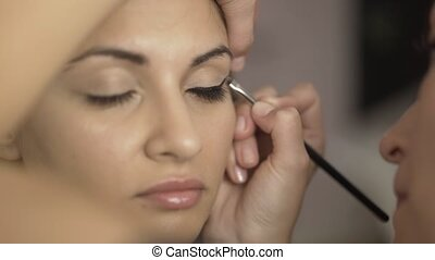 Make up artist applying toning cream to a girl s eye area