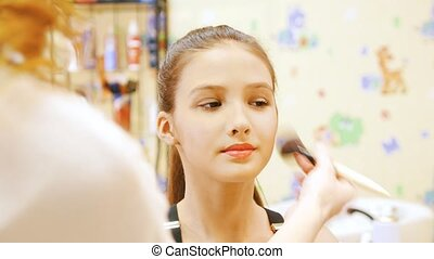 Make up artist causes the powder on the face of a young...