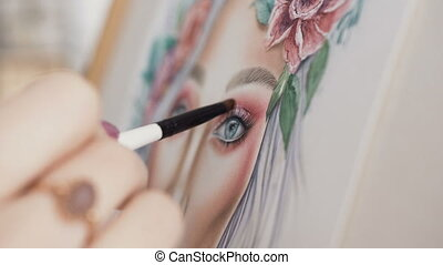 Make-up artist comes up with makeup using a face chart. The artist makeup paints face woman on paper and smears a small brush using palette of eyeshadows for eyes