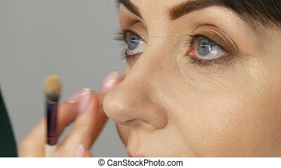 Make up artist do eye makeup to middle-aged woman with blue eyes. Age makeup. Close-up portrait. Apply powder with brush