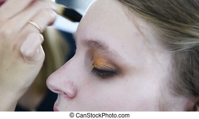make-up artist doing make-up beautiful girl in the salon,...