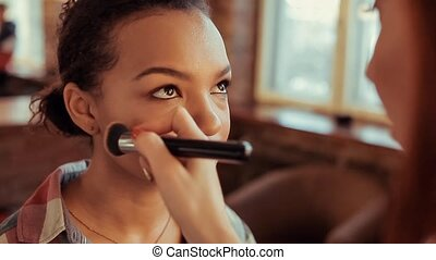 Make up artist doing make up using profesional makeup brush.