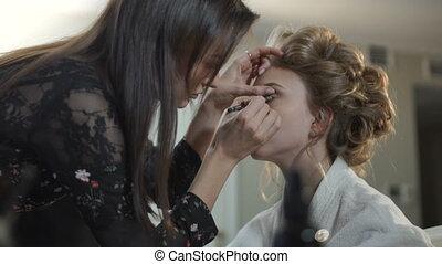 Make-up artist doing makeup bride
