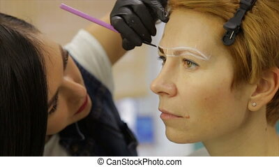 Make-up artist makes eyebrow tattoo for a woman - Master in...