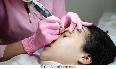 make-up artist makes eyebrow tattoo for girl - make-up...