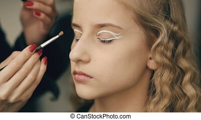 Make-up artist makes young actress girl beautiful makeup for eyes before dancing perfomance indoors
