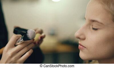 Make-up artist makes young actress girl beautiful makeup for face before dancing perfomance indoors