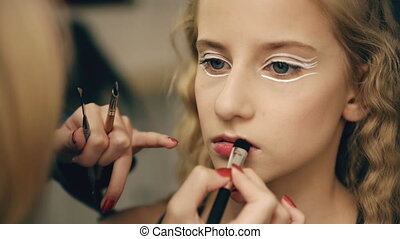 Make-up artist makes young actress girl beautiful makeup for lips before dancing perfomance indoors