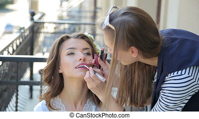 Make up artist paints lips for bride