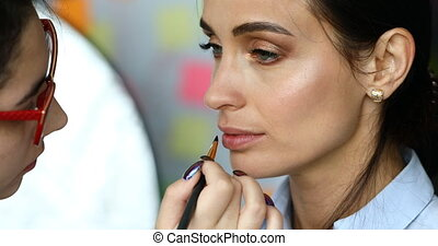 Make-up artist paints lips of a woman model before shooting