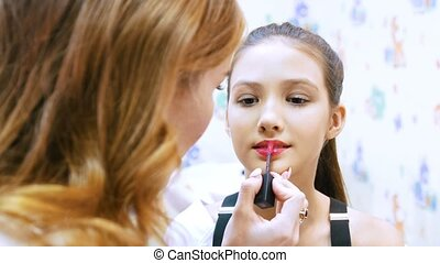 make-up artist paints nice young girl's with cream lipstick