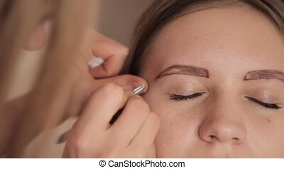 Make-up artist plucking eyebrows for female client.