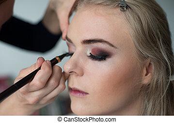 Make-up artist prepearing model