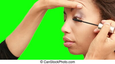 Make up artist putting mascara on models face on green...