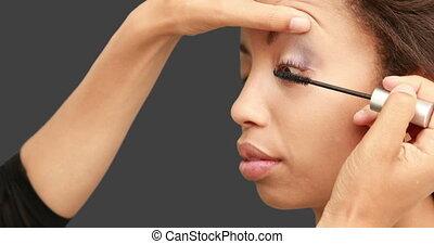 Make up artist putting mascara on models face on grey screen...