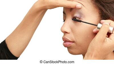 Make up artist putting mascara on models face on white...