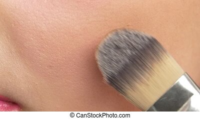 Make-up artist using brush and making blusher on her cheeks, close up, slow motion