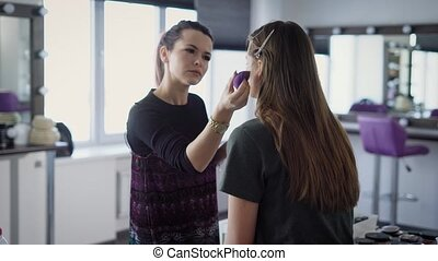 Make-up artist, who works in the studio, confident foundation deals with the help of a professional sponge on face a quiet model with long auburn hair, which removed the clamps to keep it out in face
