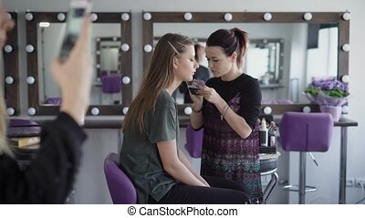 Make-up artist with hair retracted in a ponytail, wearing a dress and a black jacket puts on eyelids eye shadow model with long dark hair. Nearby sits a young girl with blond hair that makes selfie