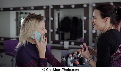 Make-up artist with hair retracted in the tail causes sponge-eye concealer for a girl who is talking on the trendy phone with her agent who is fined work for her. Model enjoys the new proposal