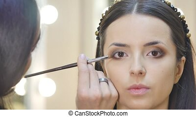 Make-up artist work on her friend. Real people