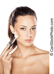 make up - beautiful young woman apply makeup on her face