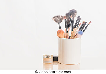 make up brushes in holder and cosmetics isolated on white