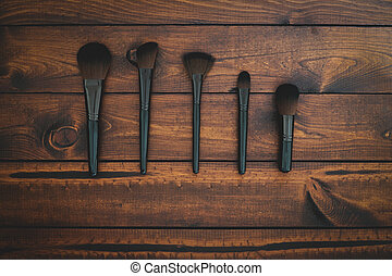Make-up brushes on a brown background