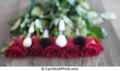 Make up brushes on pile of roses