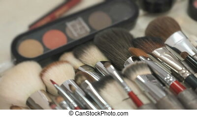 Make-up cosmetic palette and brushes on table