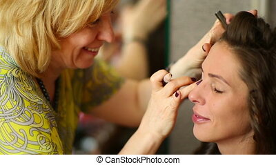 Make-up - Makeup artist apply the cream on the eyelids...