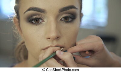 Make up for young beautiful woman, applying lipstick pencil