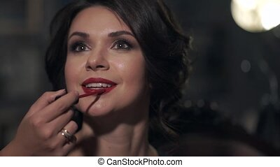 Make-up lipstick beautiful bright girl with red lipstick on the wedding day. Model smiles broadly, visible white teeth. In the background a beautiful blur.