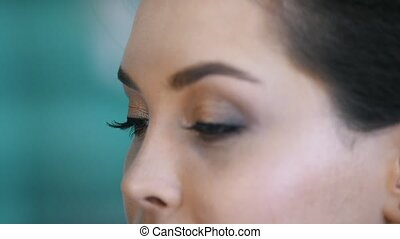 Make-up process at beauty shop for young black haired woman...