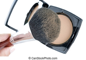 Make-up brush on powder-case with mirror. Selective focus on...